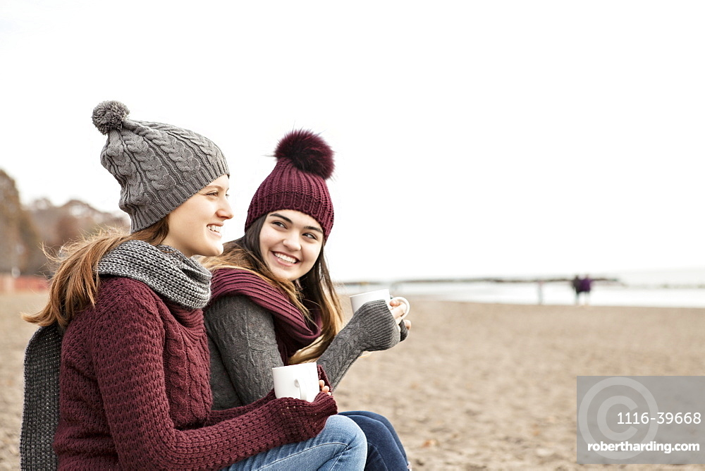 Two friends at the beach wearing knit hats and scarves, sitting and having coffee together, Woodbine Beach, Toronto, Ontario, Canada