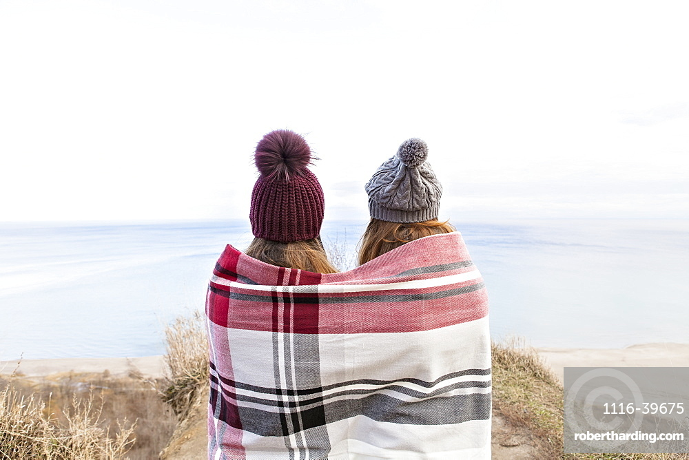 Two friends wrapped in a blanket standing on bluffs looking out over Lake Ontario, Scarborough, Ontario, Canada