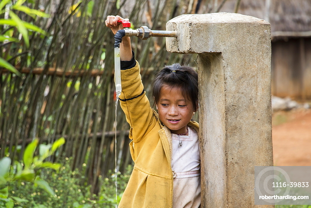 Hmong girl playing with a water tap in Na Kam Peng, also called Bomb Village, Xiangkhouang, Laos