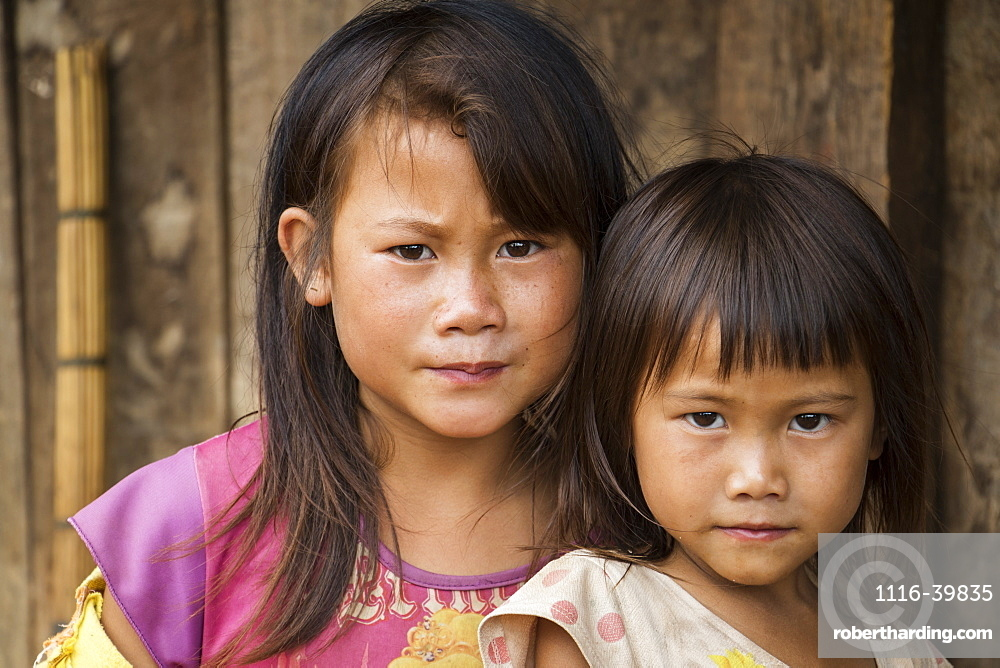 Portrait of two Hmong girls in front of their house in Na Kam Peng, also called Bomb Village, Xiangkhouang, Laos