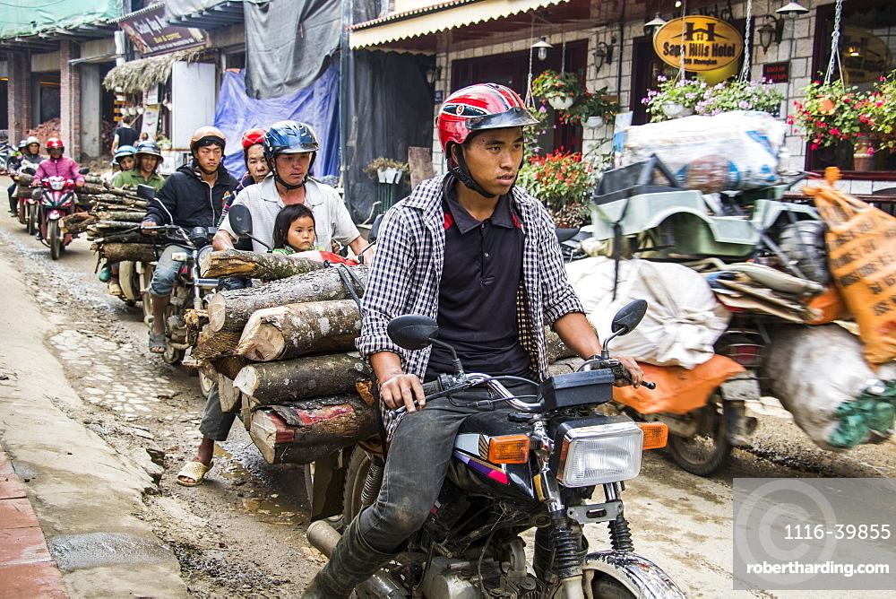 People hauling logs on motorbikes, Sapa, Lao Cai, Vietnam