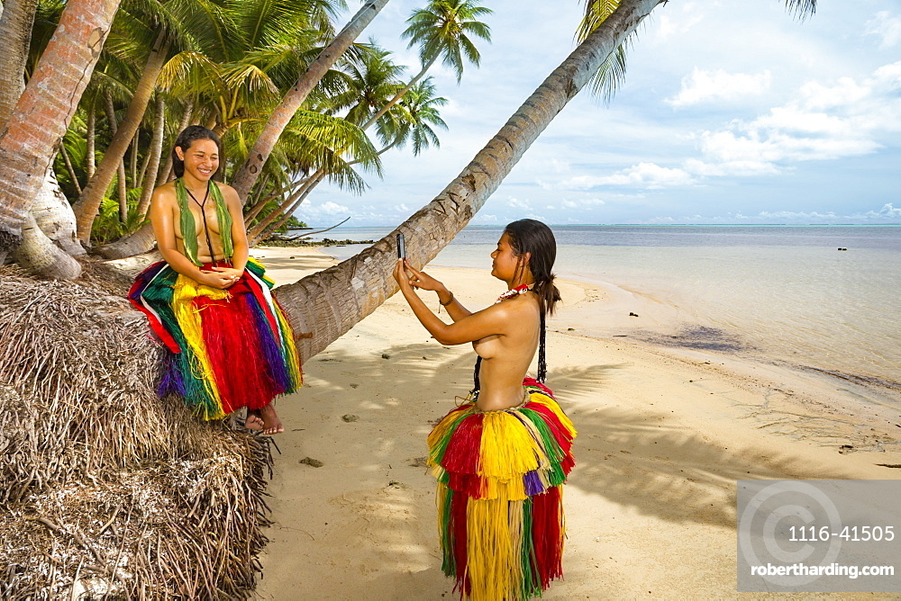 Two young women in traditional outfits for cultural ceremonies taking a photo with a smartphone on the island of Yap, Yap, Micronesia