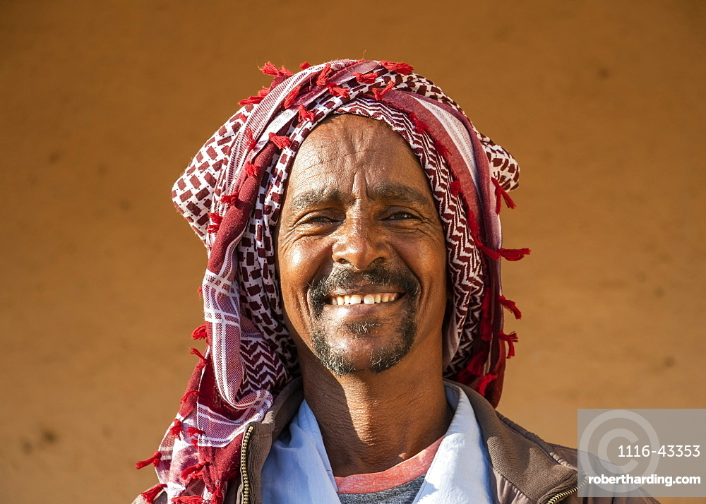 Portrait of an Eritrean man smiling with a headscarf on his head, Monday livestock market, Keren, Anseba Region, Eritrea