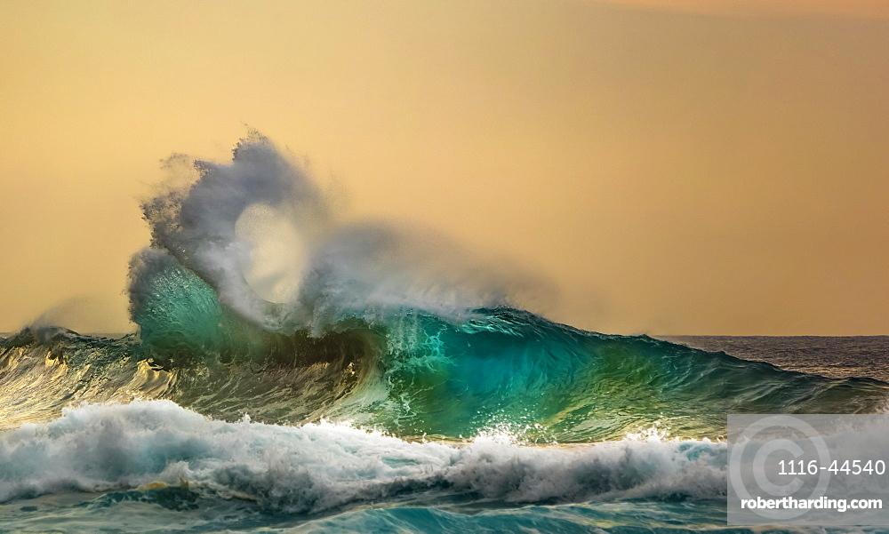 Ocean waves crashing into the shore off the Na Pali coast at sunset, Kauai, Hawaii, United States of America