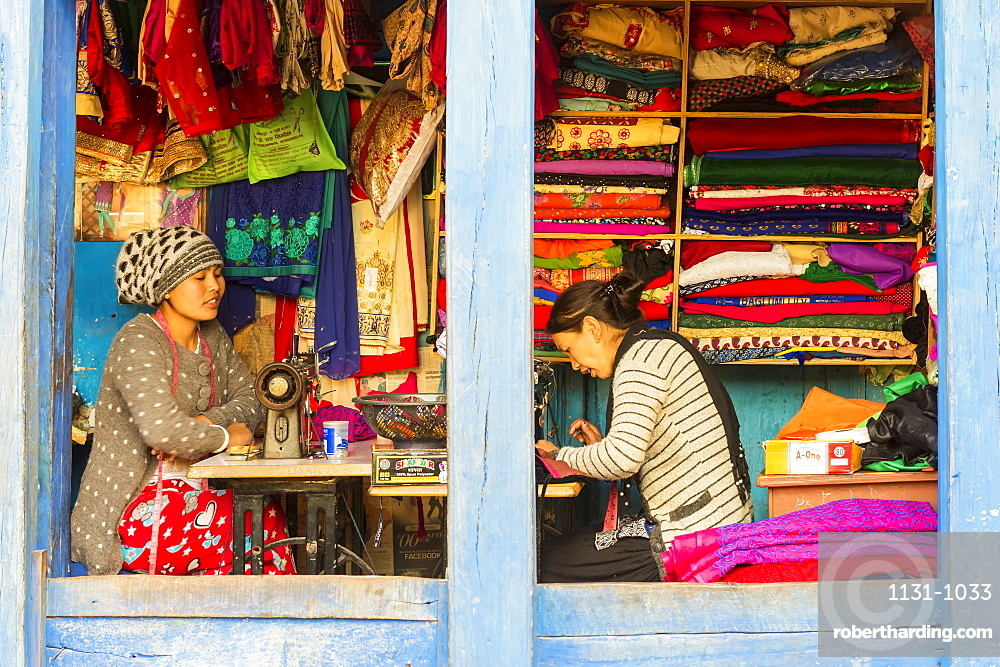 Young Nepalese women working in an open Tailor shop in Bandipur, Tanahun district, Nepal, Asia