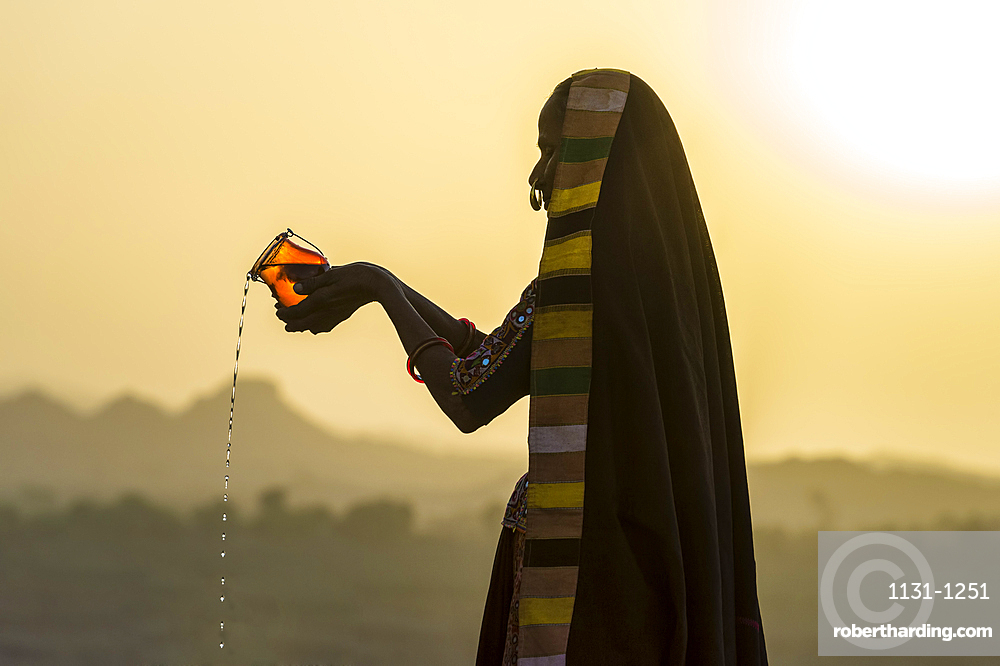 Ahir Woman in traditional colorful cloth pouring water at sunet, Great Rann of Kutch Desert, Gujarat, India