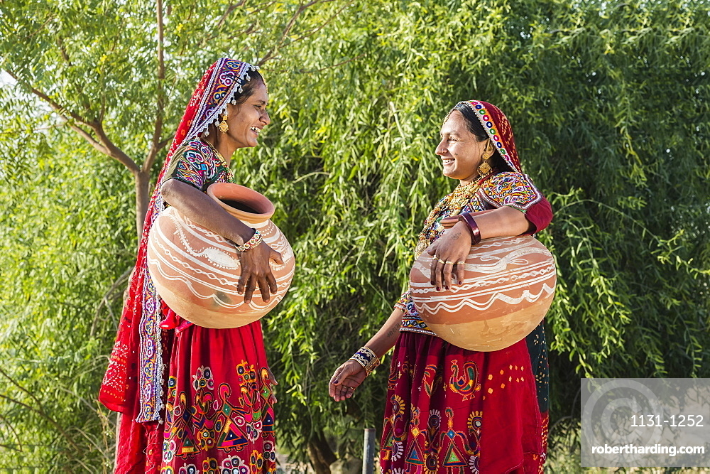 Two Ahir Women in traditional colorful clothes carrying water in a clay jug, Great Rann of Kutch Desert, Gujarat, India, Asia