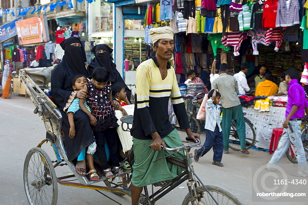 Street scene in holy city of Varanasi, young muslim women in black burkhas ride with their children in rickshaw, Benares, Northern India