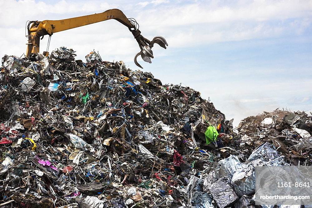 Grab machine organising metal recycling of scrap metal to avoid environmental pollution in England, United Kingdom, Europe