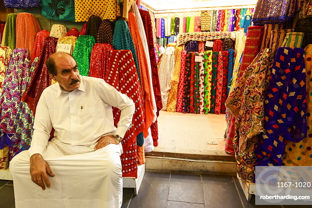 Shopkeeper seated outside his shop surrounded by  colourful material, Souq Waqif, Doha, Qatar, Middle East