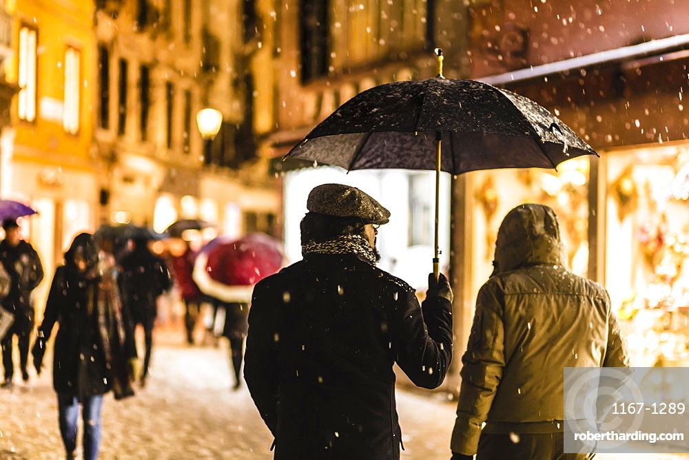 People in shopping street with umbrellas during rare snowfall, winter evening, Venice, UNESCO World Heritage Site, Veneto, Italy, Europe