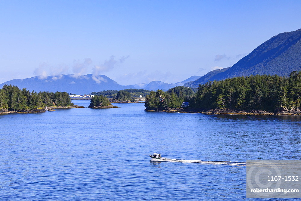 Boat travels through small forested islands, clearing morning mists, rare Summer sun, Sitka Sound, Sitka, Southeast Alaska, USA