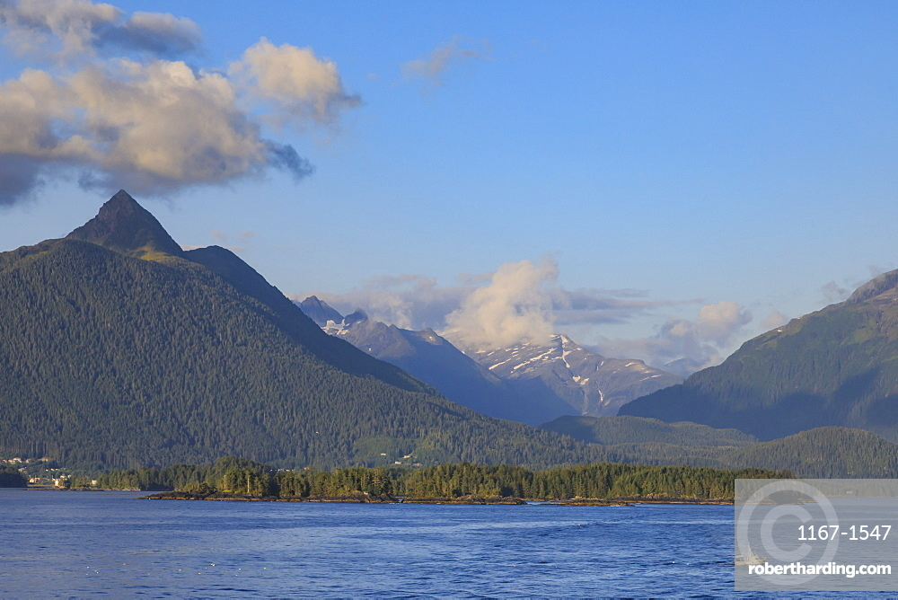 Commercial fishing vessel, forested snow-capped mountains, rare evening sun, Sitka Sound, off Baranof Island, Sitka, Alaska, United States of America, North America