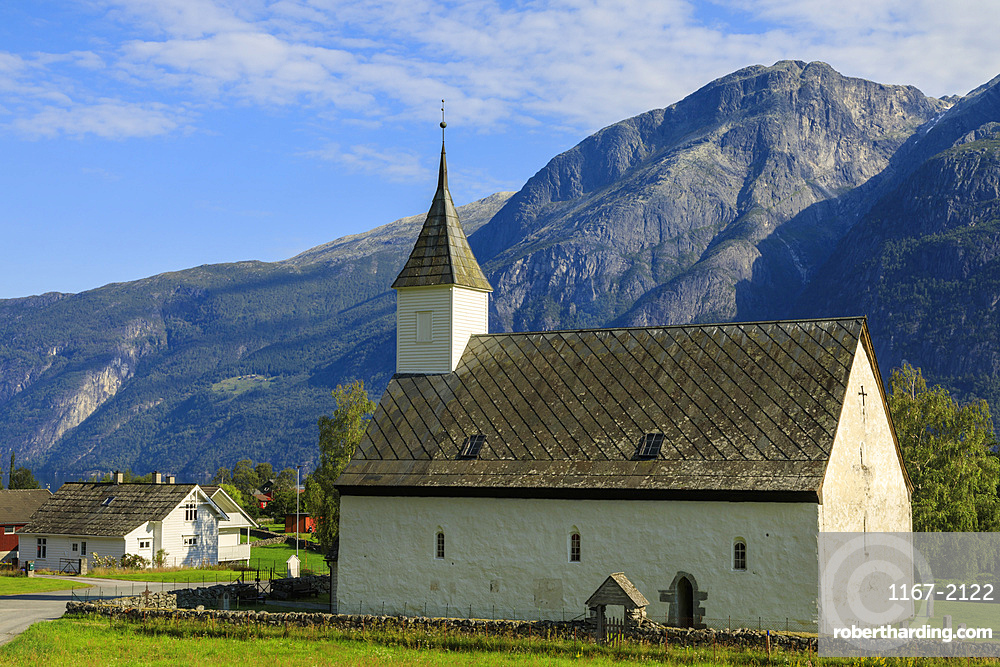 Old white church dating from 1309, sunny day, mountain and village backdrop, Eidfjord, Norwegian Western Fjords, Norway, Scandinavia, Europe