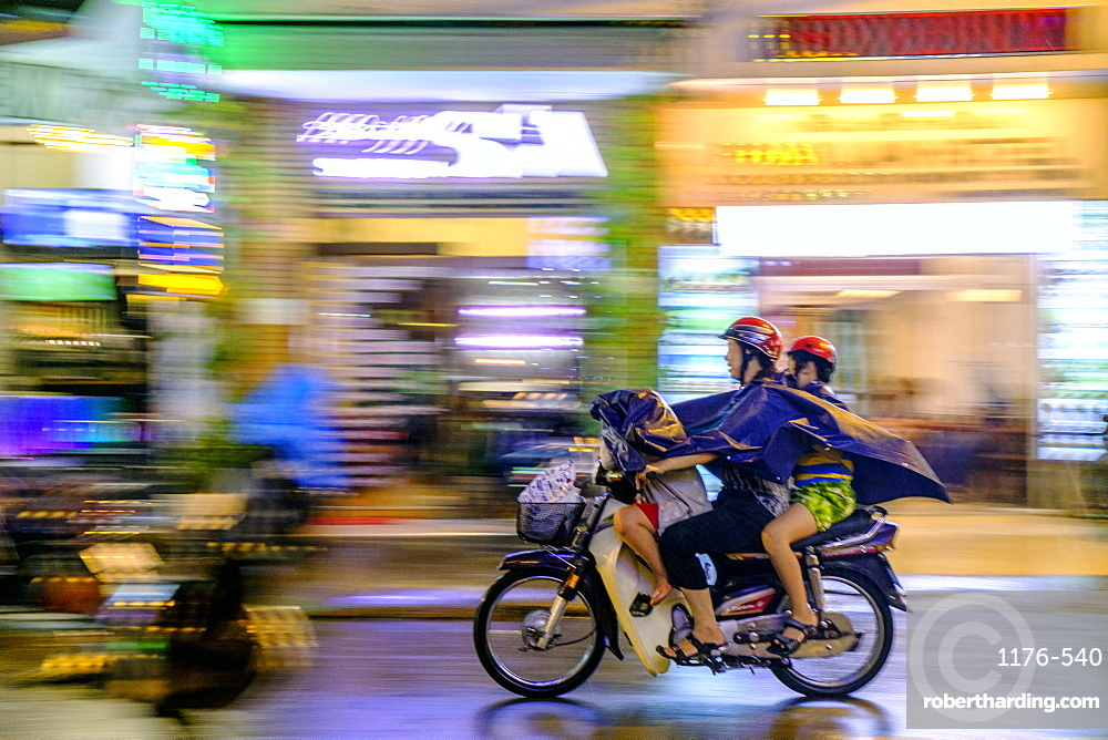 Motorbike riders in the rain in Ho Chi Minh City, Vietnam, Indochina, Southeast Asia, Asia