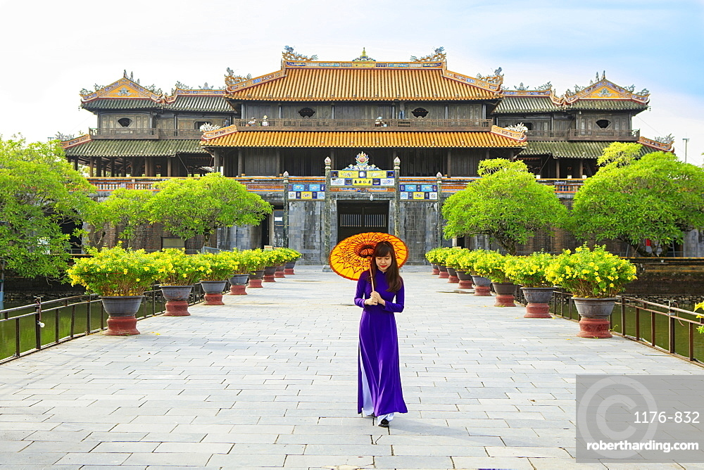 Women in a traditional Ao Dai dresses with a paper parasol in the Forbidden Purple City of Hue, A Unesco World Heritage Site