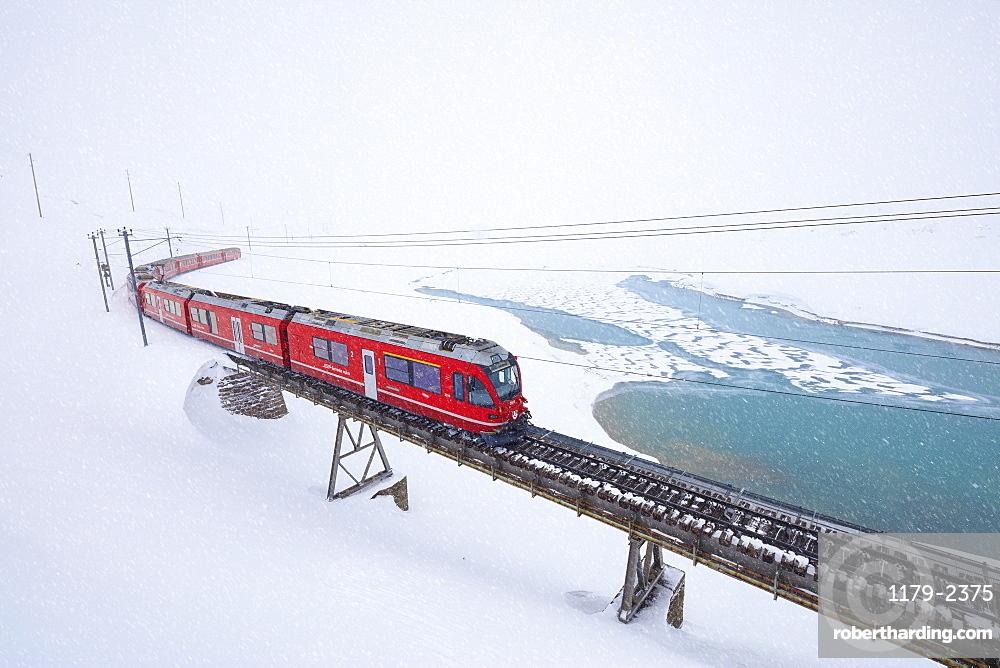 Bernina Express train at Bernina Pass under a snowfall, Engadine, Canton of Graubunden, Switzerland, Europe