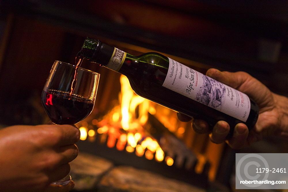 Bottle and glass of wine in front of fireplace, San Romerio Alp, Brusio, Poschiavo Valley, Canton of Graubunden, Switzerland, Europe