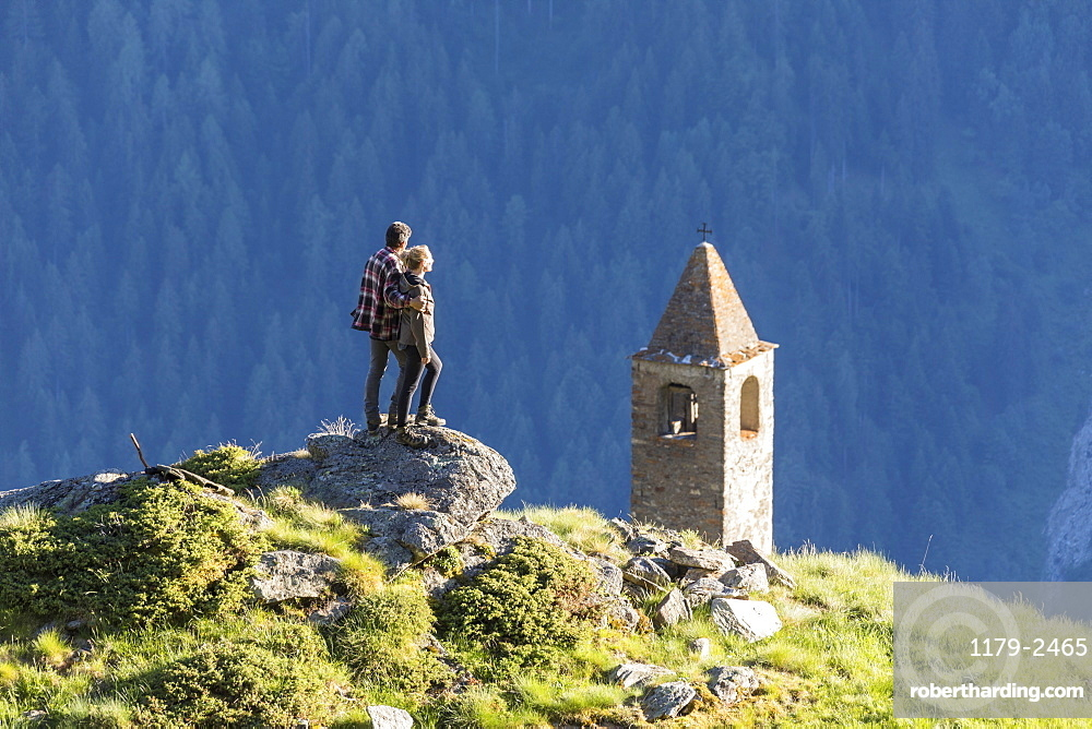 Man and woman embraced look at the bell tower, San Romerio Alp, Brusio, Poschiavo Valley, Canton of Graubunden, Switzerland, Europe