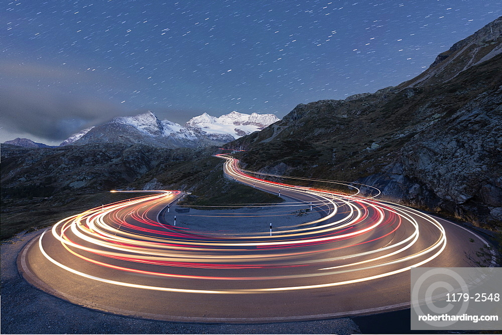 Star trail and lights of car traces, Bernina Pass, Poschiavo Valley, Engadine, Canton of Graubunden, Switzerland, Europe