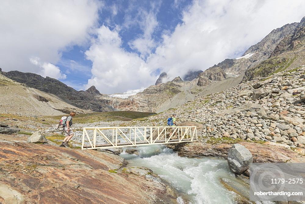 Hikers on walkway of the path Sentiero Glaciologico of Fellaria Glacier, Malenco Valley, Valtellina, Lombardy, Italy