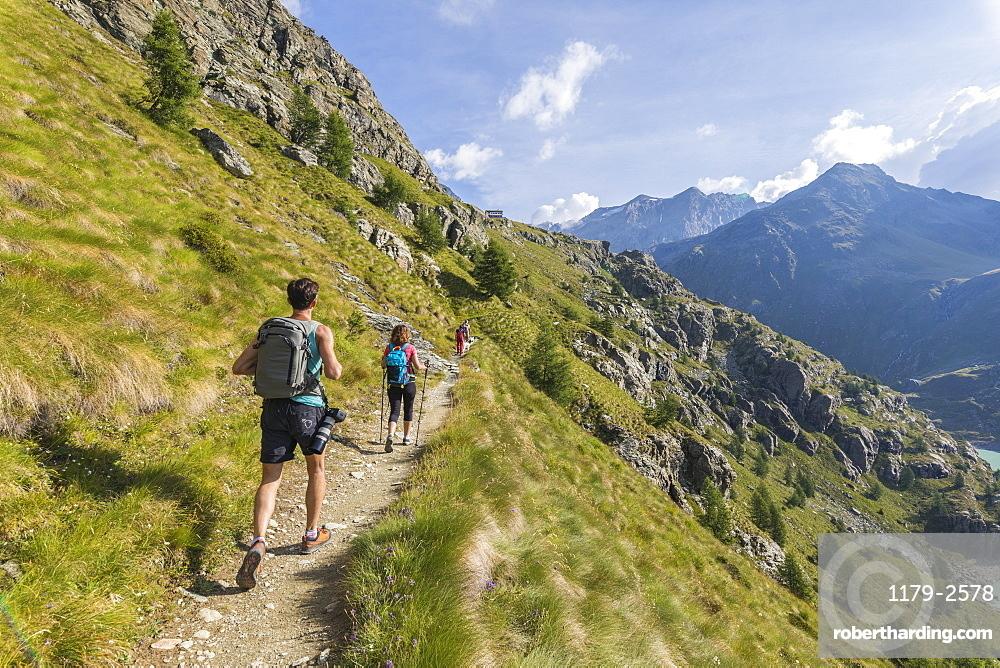 Hikers on path towards Rifugio Bignami, Malenco Valley, Valtellina, Lombardy, Italy