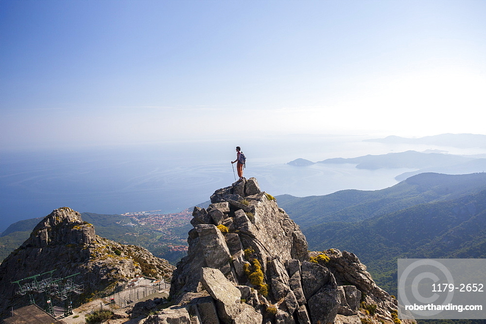 Hiker admires the sea from the top of Monte Capanne, Elba Island, Livorno Province, Tuscany, Italy, Europe