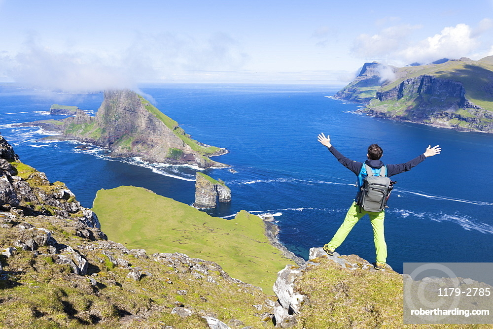 Man on cliffs looks towards Drangarnir rock, Vagar Island, Faroe Island, Denmark, Europe