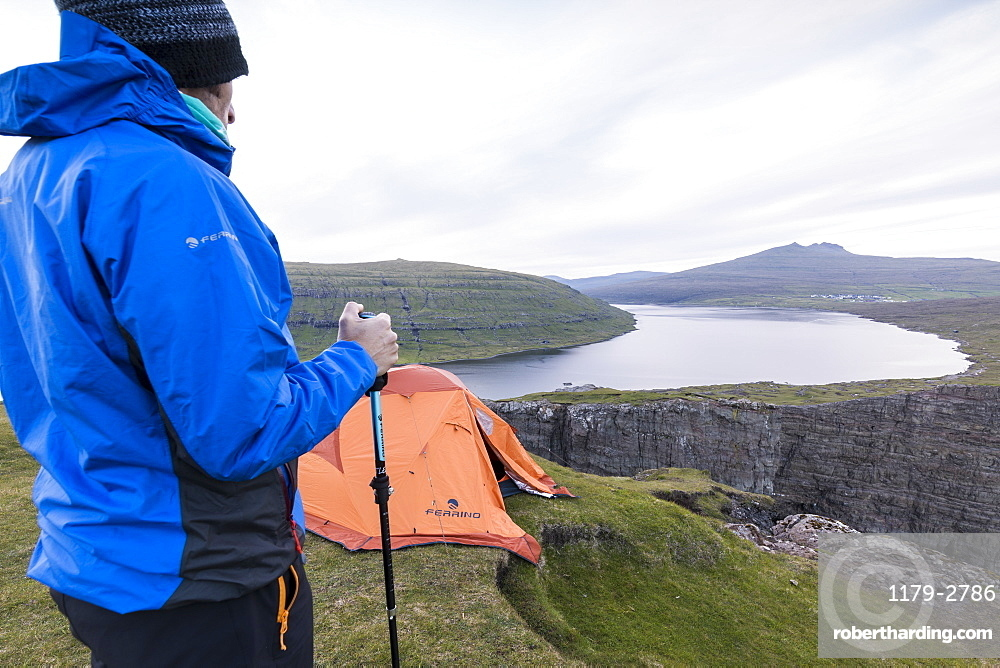 Hiker on cliffs looks towards lake Sorvagsvatn, Vagar Island, Faroe Islands, Denmark, Europe
