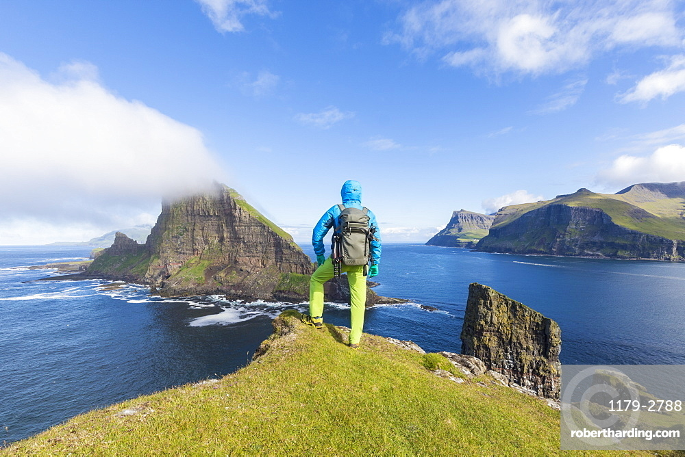 Man looks towards the sea stacks of Drangarnir and Tindholmur islet, Vagar Island, Faroe Islands, Denmark, Europe