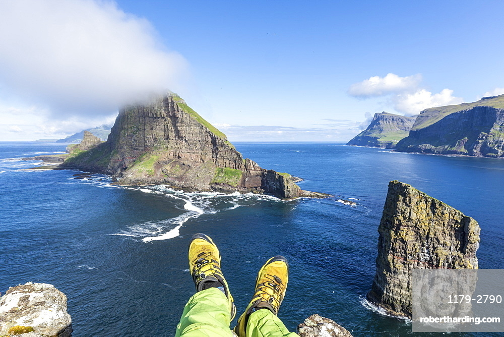 Man lays down on cliffs above the sea stacks of Drangarnir and Tindholmur islet, Vagar Island, Faroe Islands, Denmark, Europe