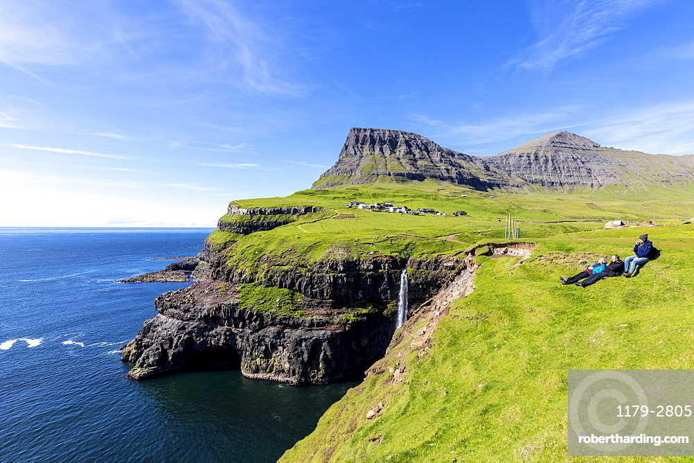 People admire the ocean from green meadows on cliffs, Gasadalur, Vagar Island, Faroe Islands, Denmark, Europe