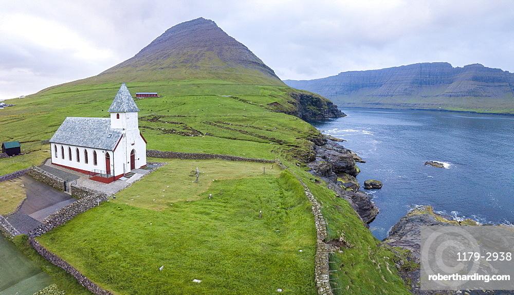 Panoramic of Church of Vidareidi by the sea, Vidoy Island, Faroe Islands, Denmark, Europe (Drone)