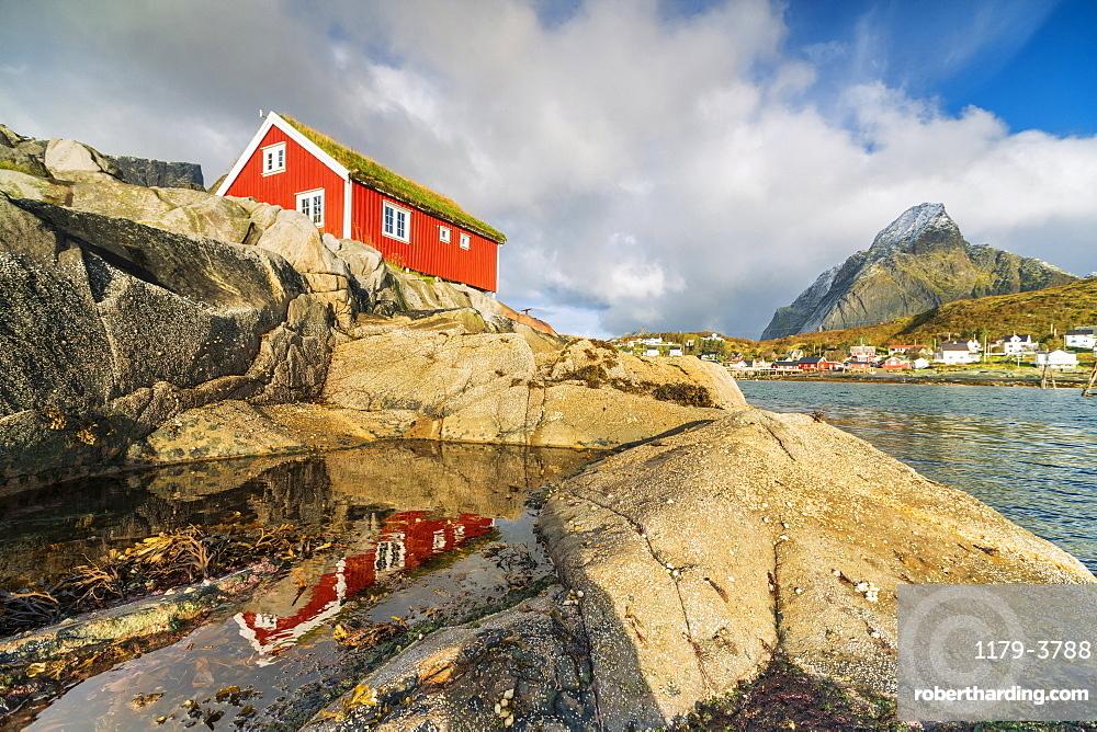 Red cabin by seaside rocks in Reine, Moskenes, Nordland, Lofoten Islands, Norway, Europe