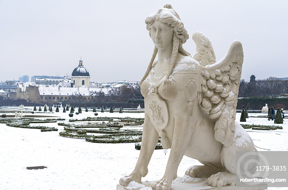 Mythological statue in the snow covered Belvedere Garten, gardens of castle housing an art museum, Vienna, Austria