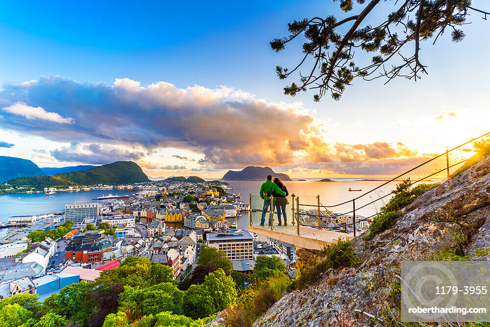 Couple embracing and holding enjoying the view of Alesund at sunset from Byrampen viewpoint, More og Romsdal county, Norway