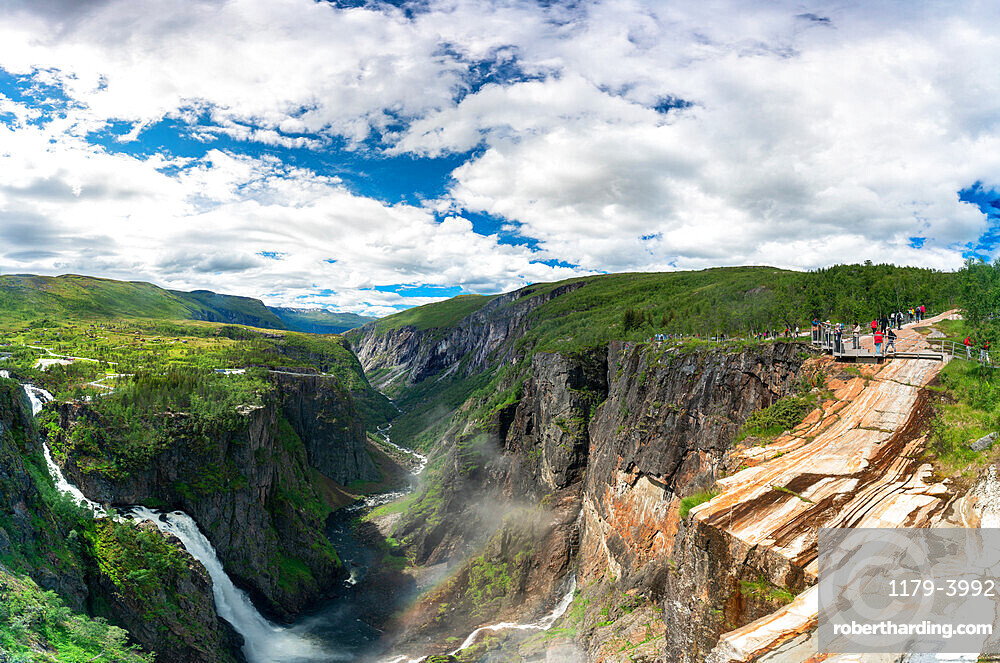 Hikers admiring Voringsfossen waterfall from the above canyon, Eidfjord, Hordaland county, Norway