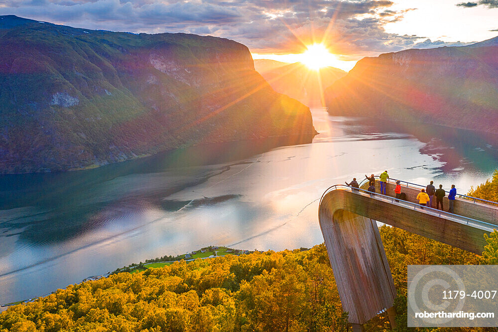 People admiring sunset from Stegastein viewpoint platform above the fjord, aerial view, Aurlandsfjord, Sogn og Fjordane county, Norway (drone)