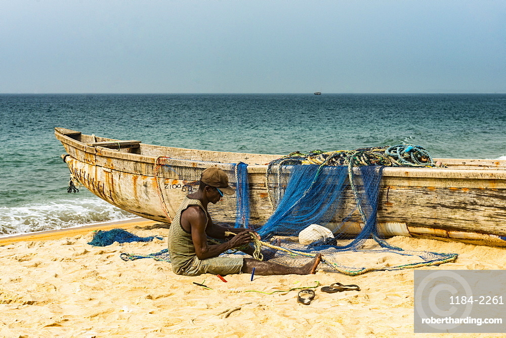 Man fixing their nets in their fishing boats on a beach in Robertsport, Liberia, West Africa, Africa