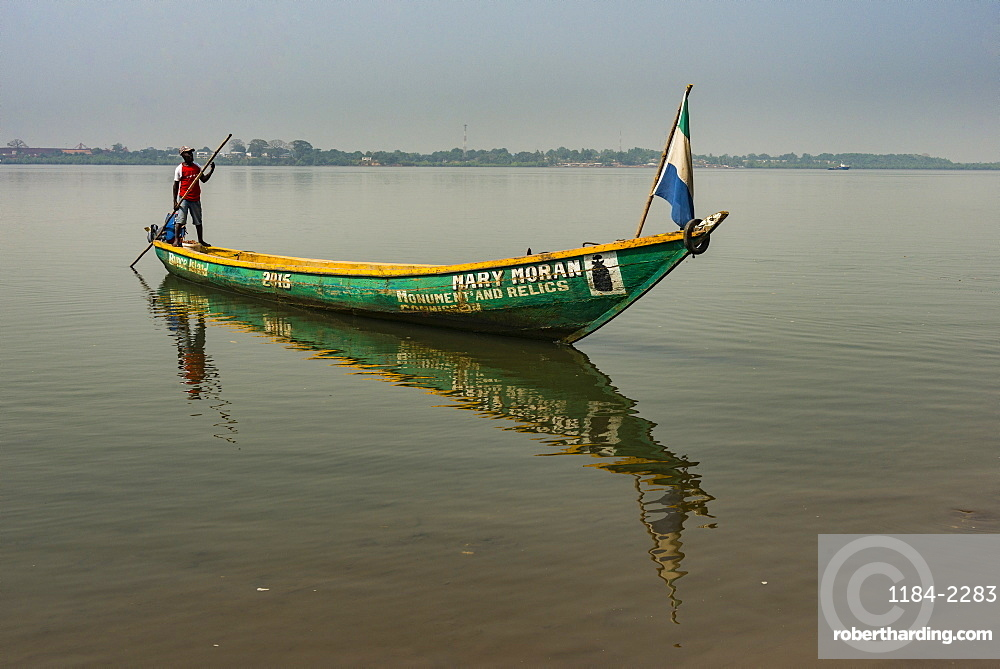 Man on his little boat before the former slave colony on Bunce island, Sierra Leone, West Africa, Africa