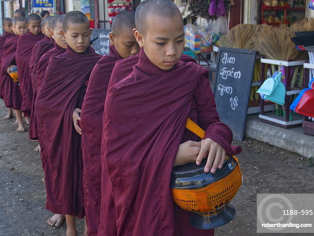Young monks receiving food gifts in Bagan, Myanmar (Burma), Asia