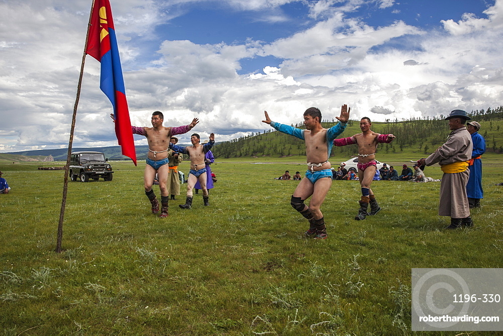 The wrestlers display their strong physique in a warm up Eagle Dance whilst their coaches announce their heroic deeds, Bunkhan, Bulgam, Mongolia, Central Asia, Asia