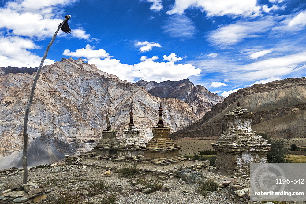 Weathered Buddhist chortens at Neyrak village looking over cliff. Grey Chorten??? Underground spiritsWhite Chorten ???God RealmYellow Chorten - Earthy Realm Zanskar, India.