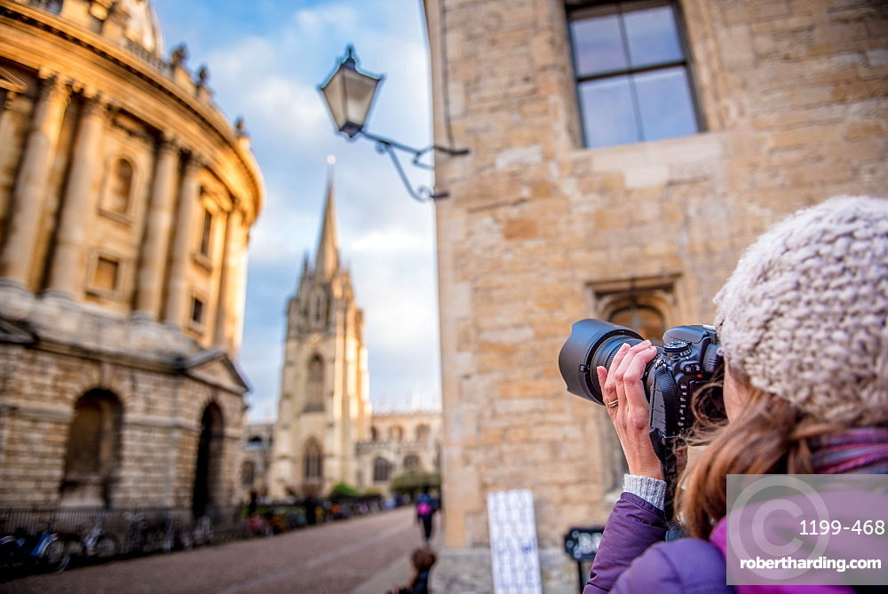 photographer photographing St. Mary's Church and The Radcliffe camera in Radcliffe Square in Oxford