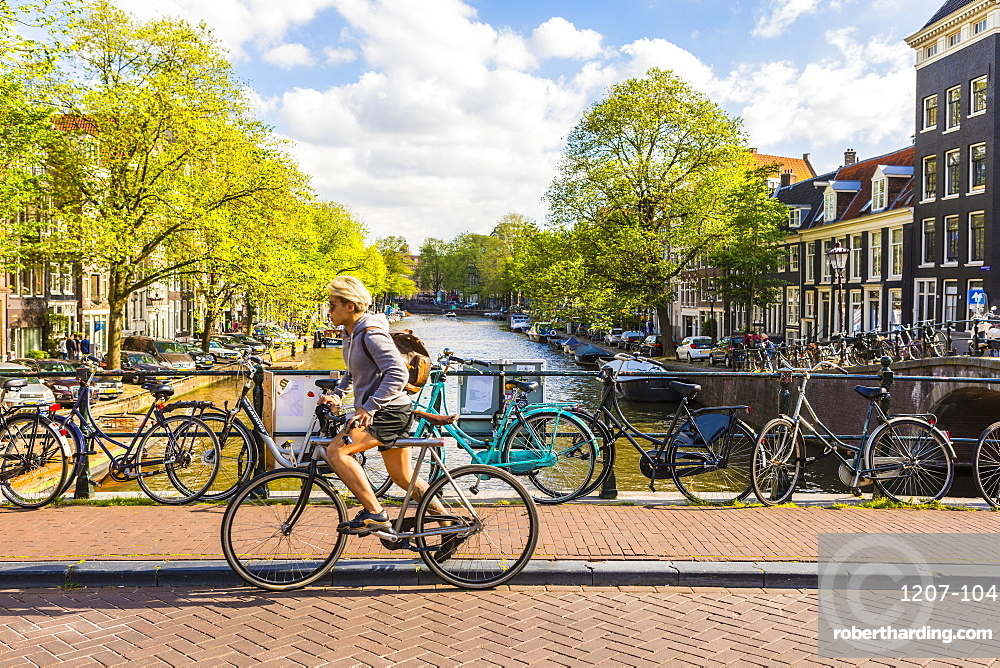 Cyclist riding over a bridge over Prinsengracht canal, Amsterdam, Netherlands