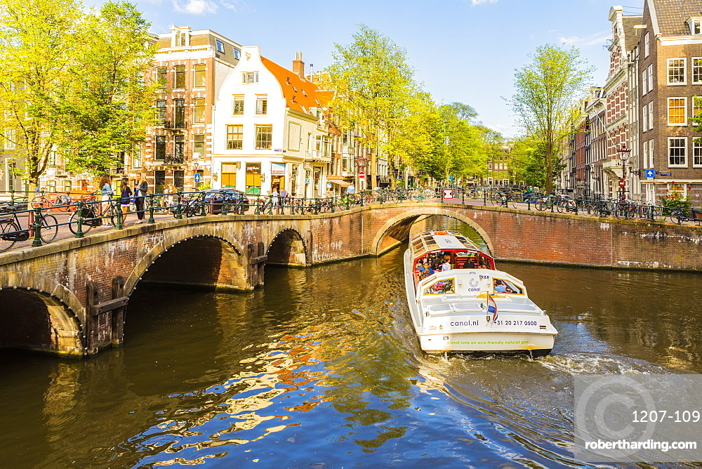 A boat going under a bridge over the Keizersgracht canal, Amsterdam, Netherlands