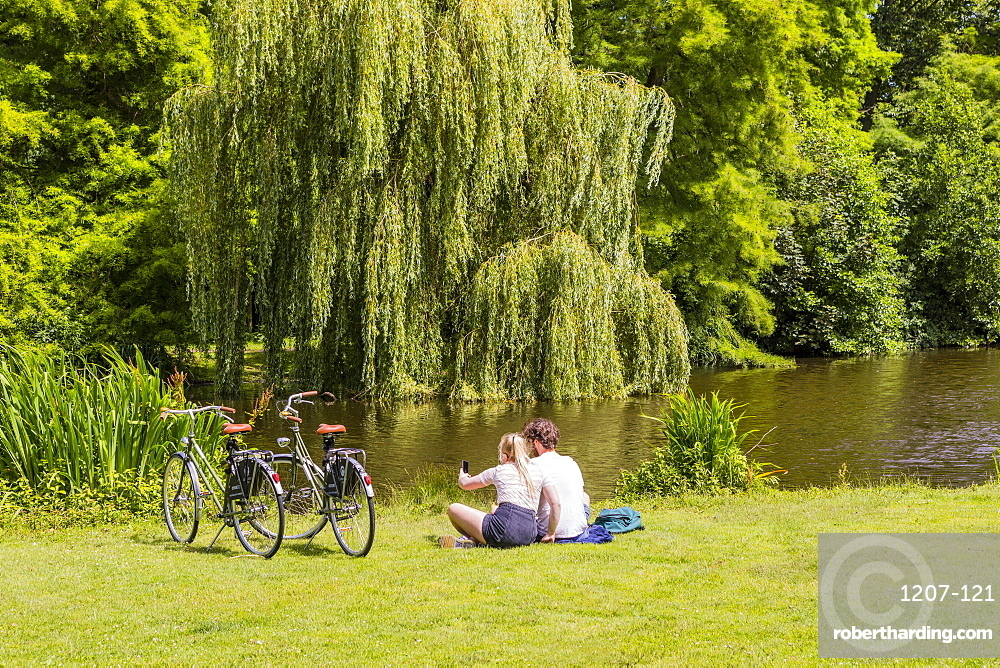 Couple sitting in Vondelpark, Amsterdam, Netherlands, Europe
