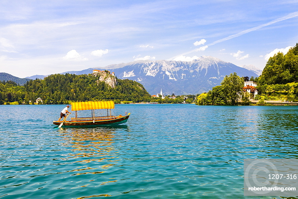 A boat in Lake Bled with Bled Castle in the background, Slovenia, Europe