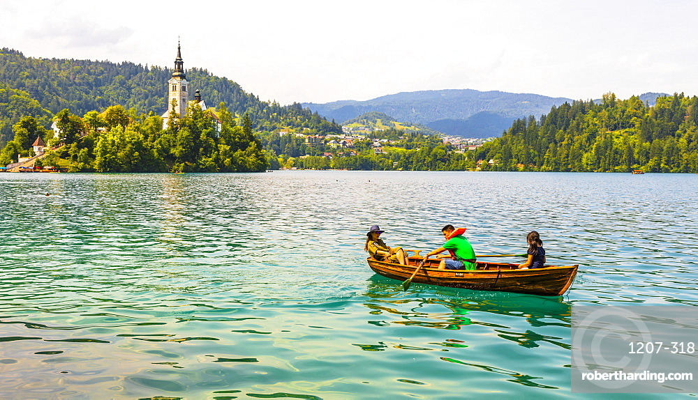 A boat on Lake Bled with the Church of the Assumption in the background, Lake Bled, Slovenia, Europe