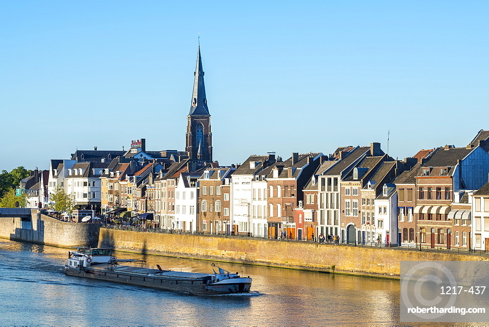 A boat passes buildings along the Meuse (Maas) River in the Wyck-Ceramique quarter, Maastricht, Limburg, Netherlands, Europe